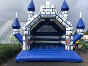 Château gonflable traditionnel multi-tours joliment décoré avec des chevaliers en armure.