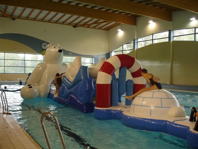 Parcours gonflable aquatique pole nord en utilisation sur une piscine avec des enfants qui jouent.