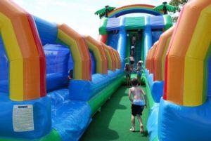 Le toboggan gonflable aquatique à piste mesure plus de 25 m de long. Les enfants en maillots de bain adorent les glissades aquatiques.