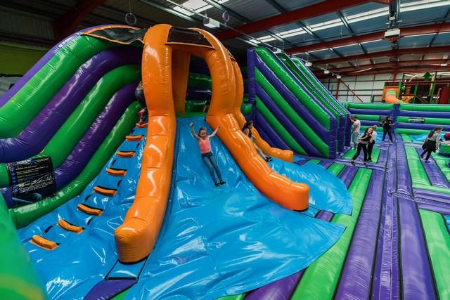Les enfants glissent sur des toboggans gonflables géants. Sur celui-ci il y a différentes faces pour encore plus de fun.