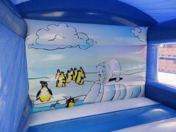 Le mur arrière intérieur de la structure gonflable maison toboggan est joliment décoré avec un thème polaire. Ours polaire et manchots sont là.