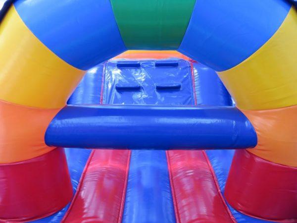 la parcours gonflable arc en ciel en 1 partie mesure 15 ma de long et propose de très nombreux obstacles de jeu. comme ici la barrière.