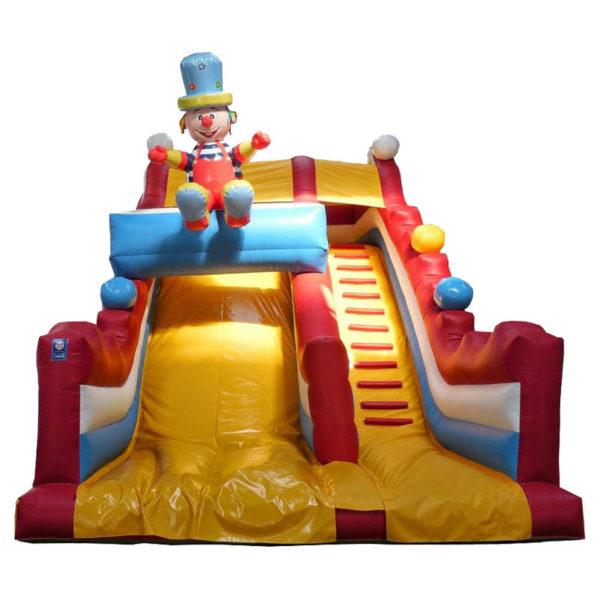 Toboggan gonflable décoré avec un sympathique clown posé sur un poutre gonflable.