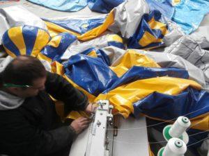 Réparation structures gonflables en couture industrielle avec machine.