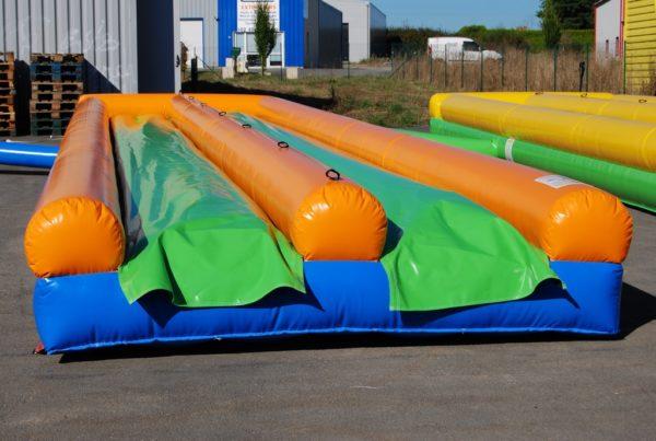 Ventriglisse gonflable double piste avec bâche de glisse en vert.